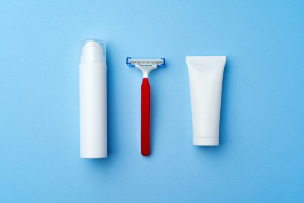 Shaving cream and disposable shaver on blue background
