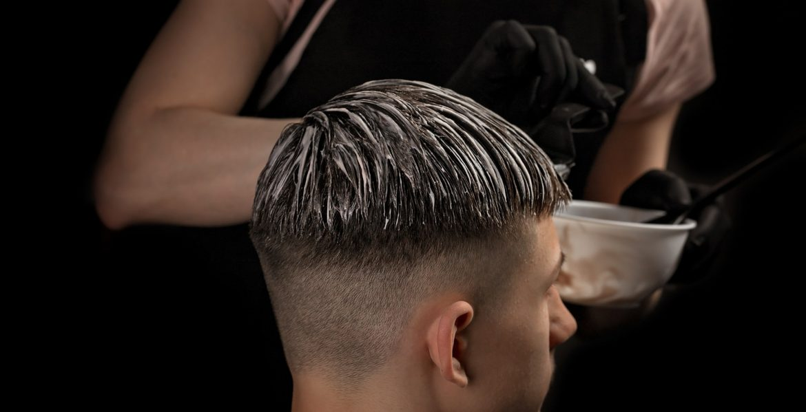 Professional hairstyle. Model and trendy hairdressed. Barber is coloring male hair.